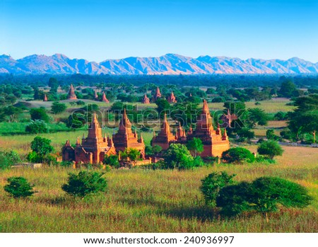 Beautiful scenic view - a lot of ancient Buddhist Temples and stupas against the background of fields, foliage, distant mountain range and clear blue sky in Bagan, Myanmar (Burma), South East Asia - stock photo