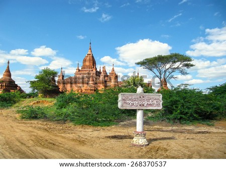 Beautiful scenic view - ancient Hindu Temple, country road fork and burmese city sign board against the background of cloudy blue sky in Bagan, Myanmar (Burma), South East Asia - stock photo