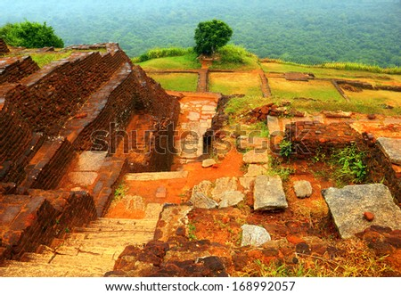 Beautiful scenic view - ancient ruined King Kassapa Palace in Sigiriya Fortress (Lion's Rock) - UNESCO World Heritage Site against the background of green wood, Sri Lanka island, South Asia  - stock photo
