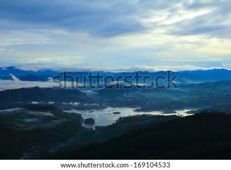 Beautiful scenic view at early morning - shadow figures of fogged mountain tops and serene lake against the background of dramatic blue sky near Sri Pada (Adam's Peak), Sri Lanka island, South Asia  - stock photo