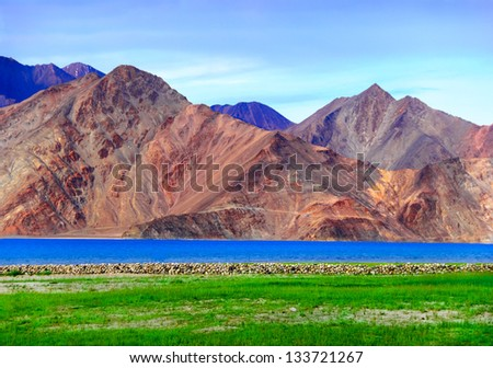 Beautiful scenic view of clean blue waters under colorful pink and purple mountain range against the background of dramatic evening sky near Pangong lake, Ladakh, Jammu & Kashmir, Northern India - stock photo