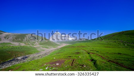 Beautiful scenic view of distant colorful mountain range and cloudy blue sky with green field - stock photo