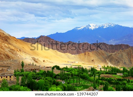 Beautiful scenic view of Leh city at summer time evening with distant colorful mountain and cloudy sky, Ladakh range, Jammu & Kashmir, Northern India - stock photo