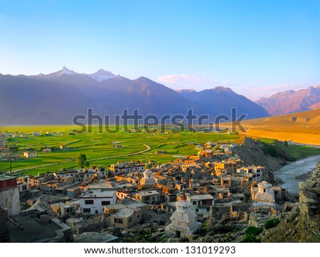 Beautiful scenic view of Padum city with traditional Tibet houses against the background of green field and purple mountain in Zanskar valley on evening, Ladakh range, Jammu & Kashmir, Northern India - stock photo