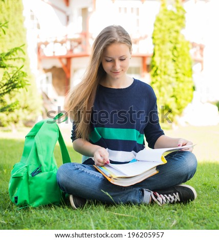 Beautiful school or college girl sitting on the grass with books and bag studying in a park. - stock photo