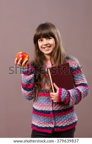 Beautiful schoolgirl is holding book and apple,she likes to have healthy snack  while she is learning.Healthy snack for beautiful schoolgirl - stock photo