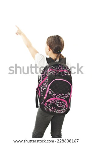 Beautiful schoolgirl with backpacks pointing at wall. Back view. Isolated on white background  - stock photo