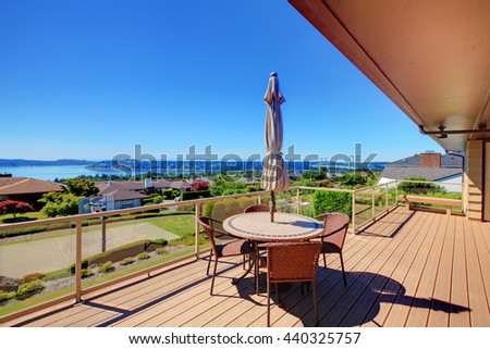 Beautiful screened walkout deck with patio table and chairs overlooking nice landscape - stock photo