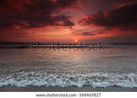 Beautiful sea beach under coudy sunset sky on Bali - stock photo