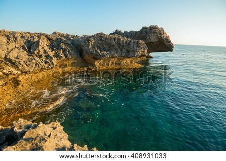 Beautiful sea landscape. Rocky shore calm sunny morning. Quiet clear sea. - stock photo