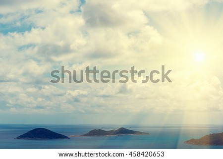 Beautiful seascape: green islands, blue water and cloudy sky in the sunlight - stock photo