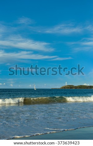 Beautiful seascape of a perfect blue sky with white clouds and calm surf breaking on the beach. White sailboat sailing out of the bay into the distance around the point. Lighthouse on the headland. - stock photo