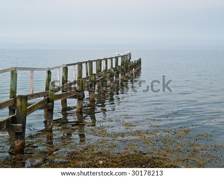 Beautiful seascape of a wooden footbridge in the middle of nowhere - stock photo