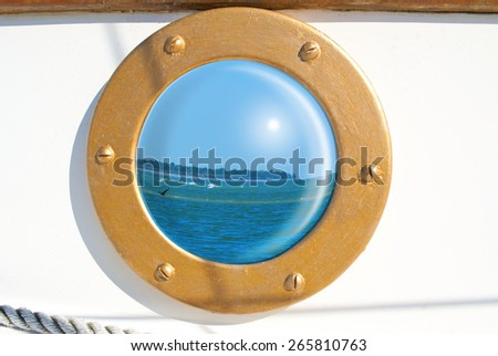 Beautiful seascape reflection in sailboat porthole - stock photo