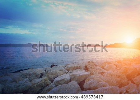 Beautiful seascape: rocky shore and calm water at sunrise or sunset. Toned - stock photo