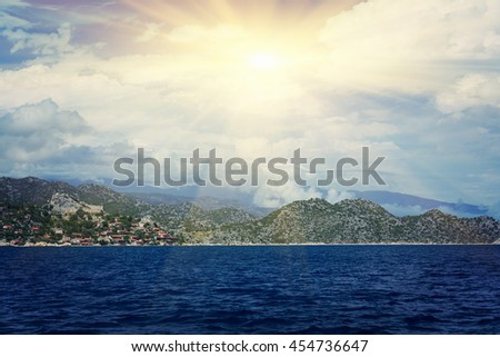 Beautiful seascape: ruins of an ancient fortress and houses with red roofs on a rock by the sea in the sunlight - stock photo