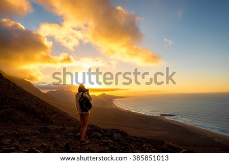 Beautiful seascape view on Cofete coastline with young female traveler on the sunset on Fuerteventura island in Spain. General plan with a lot of space - stock photo