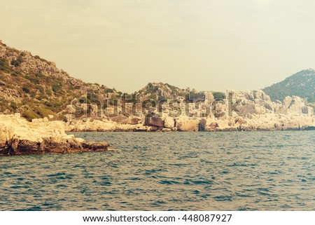 Beautiful seascape: water and rock. Toned - stock photo