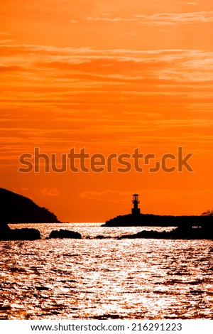 Beautiful seascape with silhouette lighthouse on sunset - stock photo