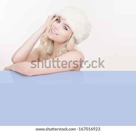 Beautiful seductive blond woman in cool winter white wearing a fashionable fur hat and leaning on a blank blue placard with an enticing smile, copyspace for your text - stock photo