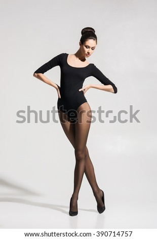 Beautiful, seductive woman posing in hosiery and heels over white background. - stock photo