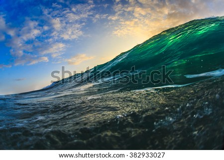 Beautiful semitransparent seascape at sunset time. Big surfing translucent green ocean wave with sun spot. Marine sport water surface. - stock photo