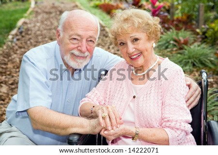 Beautiful senior couple outdoors.  The wife is in a wheelchair. - stock photo