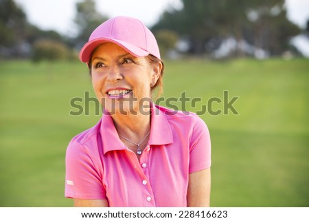 beautiful senior female golf player on a golf course - stock photo