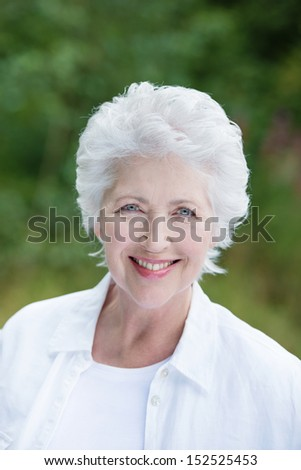 Beautiful senior lady with a beaming friendly smile standing outdoors in a lush green garden or park - stock photo