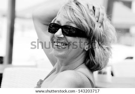 beautiful senior woman on summer vacation at sea - stock photo