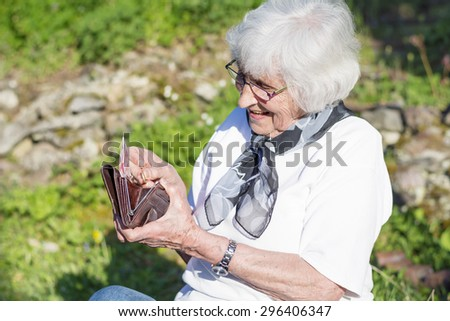 beautiful senior woman with white hair sitting in the garden counting the money in her wallet - stock photo
