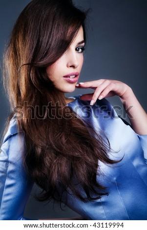 beautiful sensual brunette portrait  in blue shiny dress, studio shot - stock photo