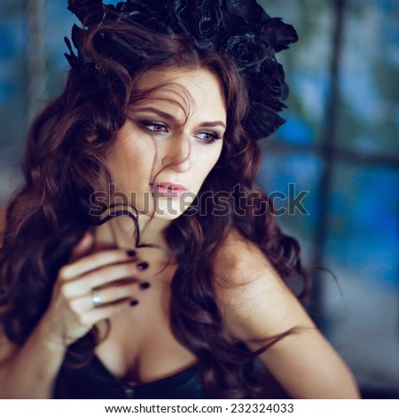 Beautiful sensual brunette with a wreath of black flowers sitting on a blue background and looking away, close up - stock photo