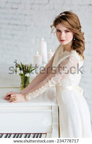Beautiful sensual girl bride in a wedding dress costs about white piano - stock photo