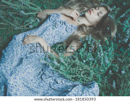 Beautiful sensual lady lying on flower meadow - stock photo