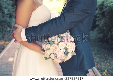 Beautiful sensual wedding couple and gentle bouquet of flowers, groom hugging lovely bride outdoors - stock photo