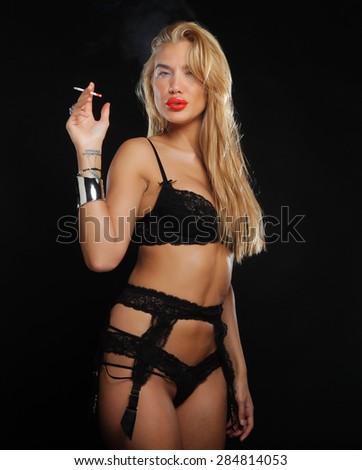 Beautiful sensual woman in black lingerie smoking a cigarette - stock photo