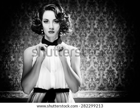 Beautiful sensual woman in blue vintage room toned image. Studio lights - stock photo