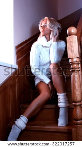 Beautiful sensual woman sitting on the wooden stairs in the house, she was wearing a white warm sweater and white stockings - stock photo