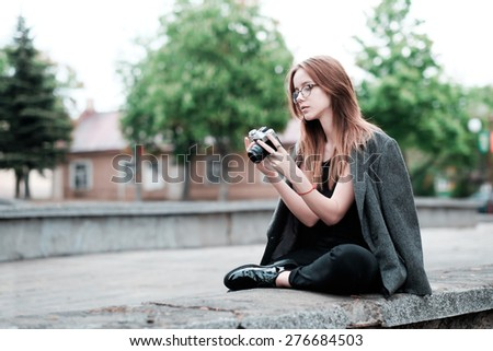 beautiful sensual young hipster girl in glasses with a camera in hand - stock photo