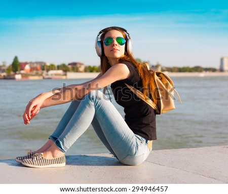 beautiful sensuality brown hair woman happy fun cheerful smiling blue sunglasses black t-shirt jeans music headphones river urban city portrait nature slim body technology device space impressions - stock photo