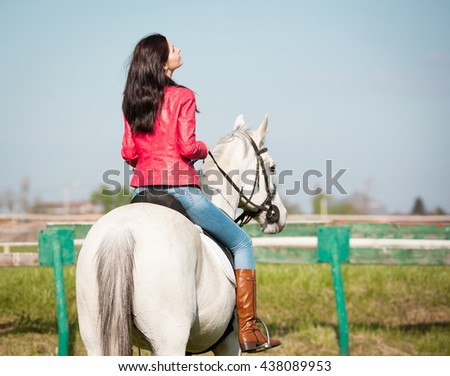 Beautiful sensuality elegance back woman cowgirl, riding a white horse. Clothed blue jeans, red leather jacket. Has slim sport body. Portrait nature. People and animals. Equestrian. American ranch. - stock photo