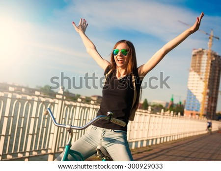 Beautiful sensuality elegance brown hair woman cyclist, has happy fun cheerful smiling face, black shirt, blue jeans. Has slim sport body. Motion on great bicycle in urban city. Portrait nature.  - stock photo