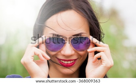 Beautiful sensuality elegance brunette hair woman, has happy fun cheerful smiling face, blue sunglasses, sexy lips, white teeth. Portrait nature urban city. Pure makeup. Sunny day. - stock photo