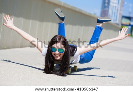 Beautiful sensuality elegance brunette hair woman, has happy fun cheerful smiling face, white t-shirt, blue sunglasses, holding skateboard. Has slim sport body. Portrait urban city. Close up - stock photo