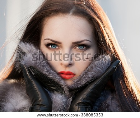Beautiful sensuality elegance brunette woman, has happy fun cheerful smiling face, blue contact lenses in eyes, fur coat, sexy lips. Portrait nature. Sunny day.   - stock photo