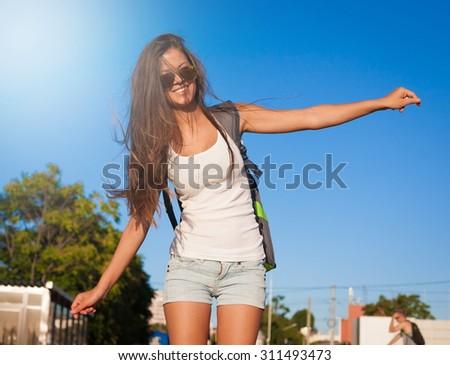 Beautiful sensuality elegance brunette woman, has happy fun cheerful smiling face, white t-shirt, blue jeans shorts, slim sport tan body. Portrait nature urban city. Sunny megalopolis - stock photo