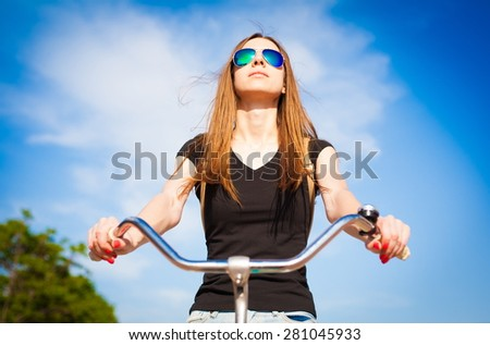 beautiful sensuality elegance lady haired woman happy fun cheerful smiling blue sunglasses black t-shirt jeans bicycle urban city portrait nature slim sport body hobby equipment riding bike cyclist - stock photo