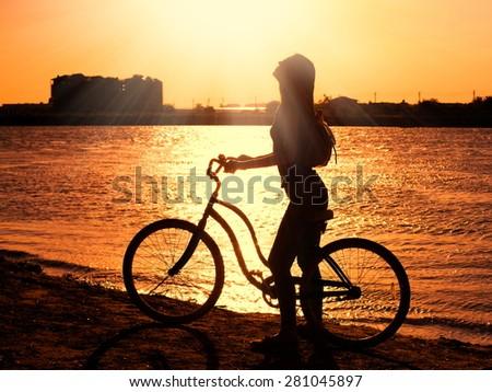 beautiful sensuality elegance lady woman happy fun bicycle urban city portrait nature slim sport body hobby equipment riding bike cyclist sunset river - stock photo