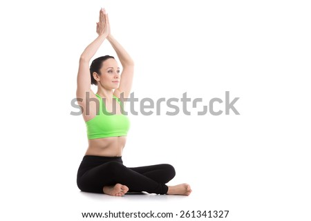 Beautiful serene girl sitting in Easy (Decent, Pleasant Pose), Sukhasana, yoga asana for lengthening spine, opening hips, meditation, breathing, hands above head, copy space - stock photo